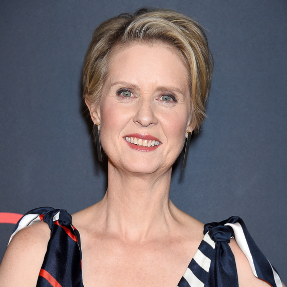 Cynthia Nixon smiling at the cameras while standing on a red carpet
