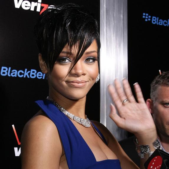 Rihanna waving at the camera on a red carpet