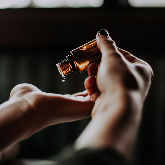 Hands applying a skincare product.
