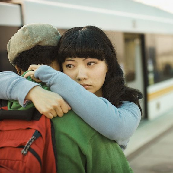 Young couple embraces at a train station