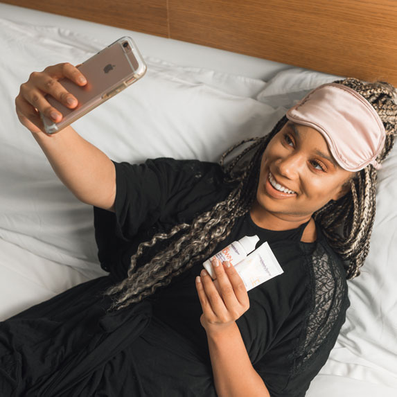 Woman poses with skincare products while taking a selfie.