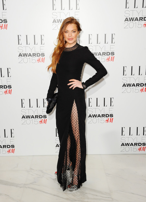 Lindsay Lohan wears a long black gown with a high slit and fishnet stockings in 2015
