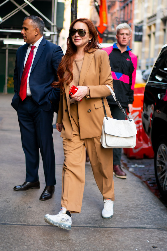 Lindsay Lohan wears a tan pantsuit with white sneakers while in New York in 2018