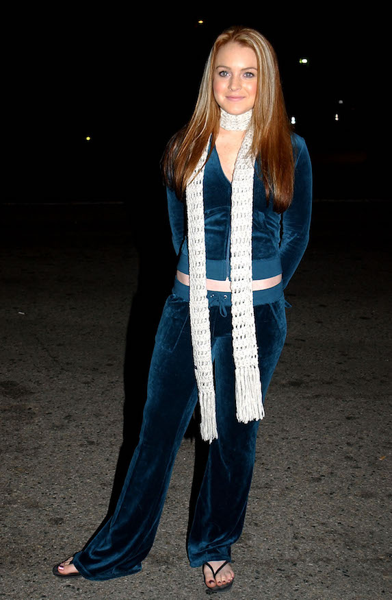Lindsay Lohan wears a velour tracksuit with a crochet scarf and flip-flops in 2002