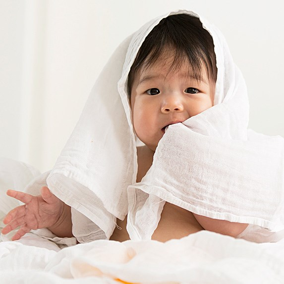 Cute Asian baby wrapped in a white cloth