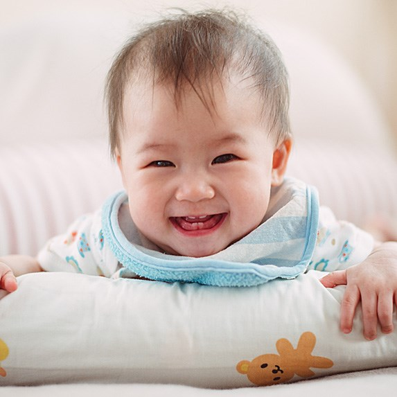 Laughing Asian baby with a wide grin and baby teeth showing