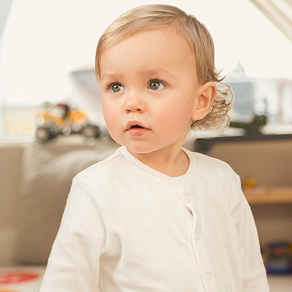 Blonde, hazel-eyed baby boy with longish hair and a white shirt looking off-camera