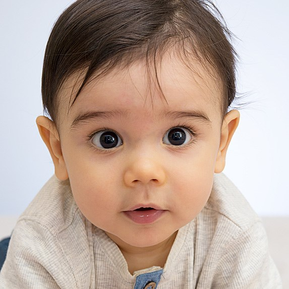 Adorable Middle Eastern baby with big brown eyes looking at the camera in wonder