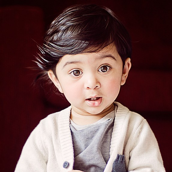 Adorable Middle Eastern toddler with side-swept dark brown hair and big brown eyes