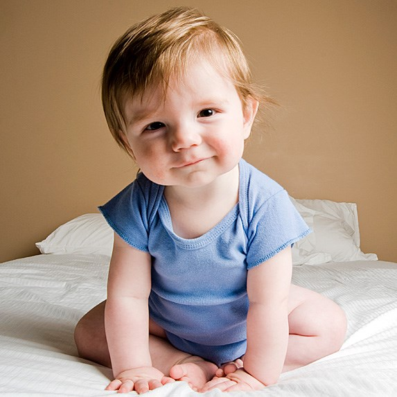 Smiling baby sitting with tipped head and strawberry-blonde hair