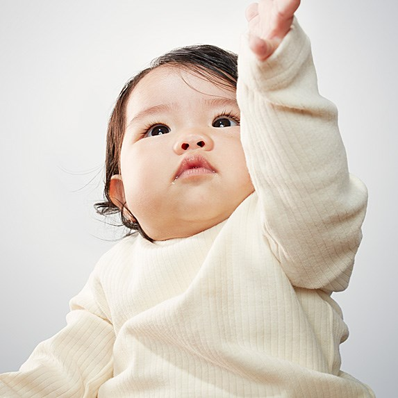 Asian baby boy holding out his hand and looking upward