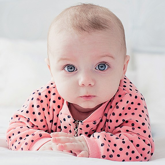 Adorable blue-eyed baby girl looking at the camera.