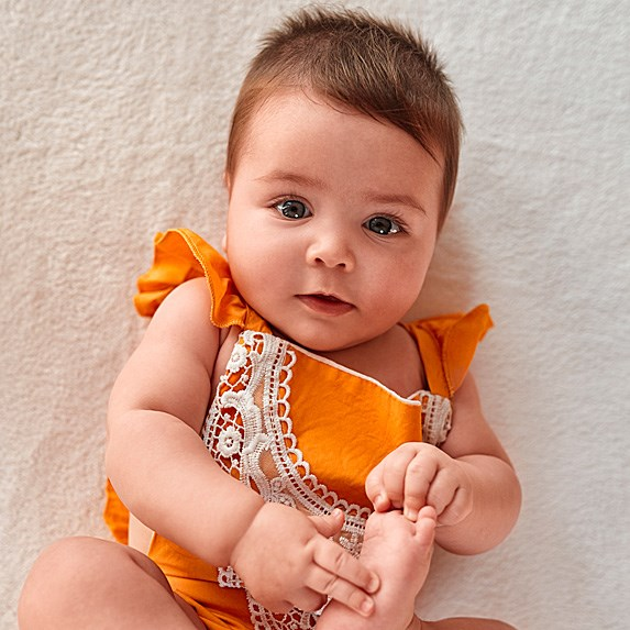 Brown-haired, blue-eyed white baby in an orange outfit laying on its back.