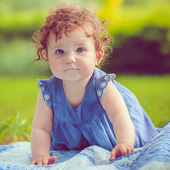 Cute red-haired baby girl with curls and a blue dress on a picnic blanket