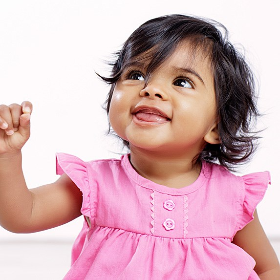 South-East Asian baby girl in a pink dress smiling, off-camera