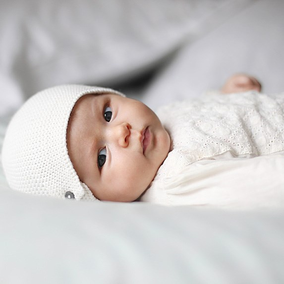 White baby laying on her back in a white hat and white outfit.