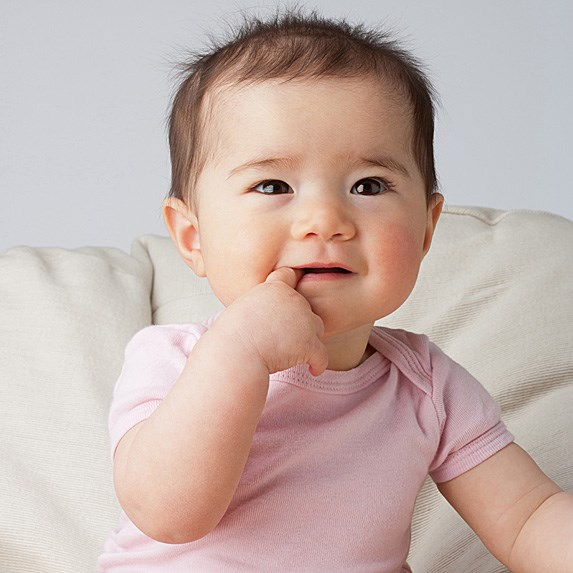 Biracial baby with a finger in its mouth
