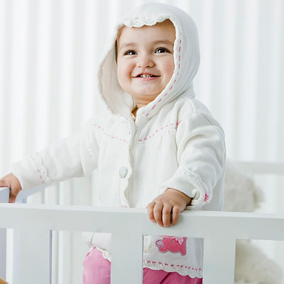 Baby in crib smiling and looking with a hoodie on.
