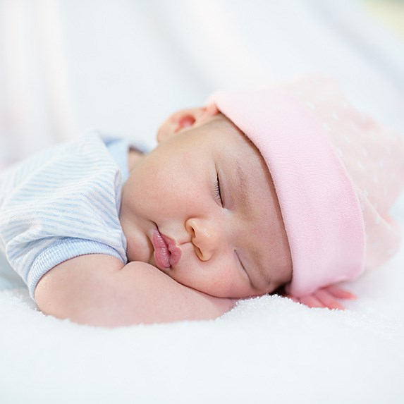 Asian baby sleeping on her forearm in a light pink hat