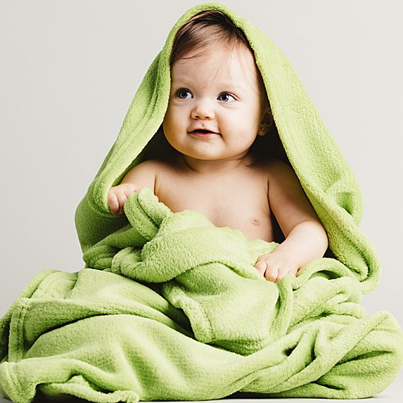 White baby girl wrapped in a lime green towel