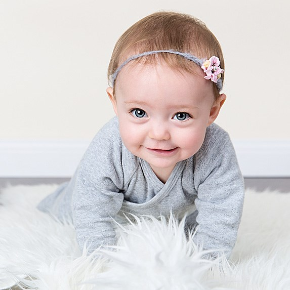 Crawling white baby girl with short light brown hair and blue eyes