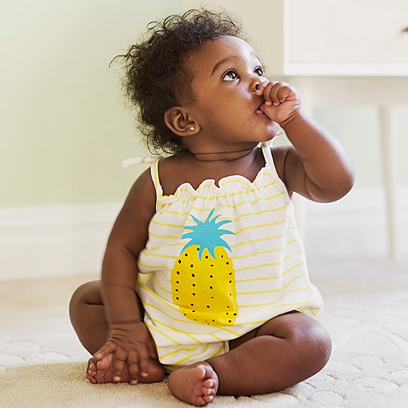 Black baby girl sitting in a pineapple tanktop and sucking her thumb looking off to the side
