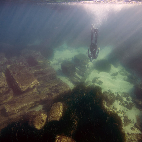 Underwater archaeologist looking at ruins