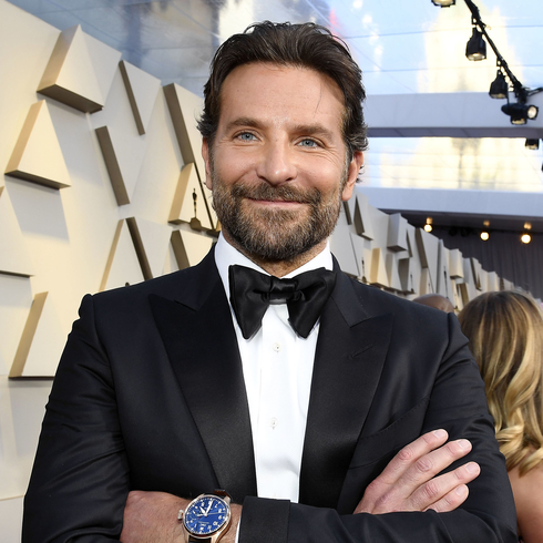 Bradley Cooper smiling with arms crossed on a red carpet