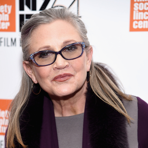 Carrie Fisher smiling in front a step and repeat