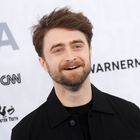 Daniel Radcliffe smiling wide on a red carpet