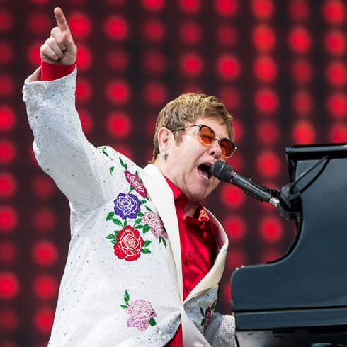 Elton John playing the piano in a white suit