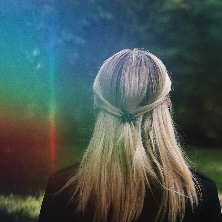 woman back turned with rainbow hued light