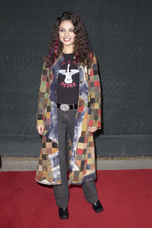 Mila Kunis wears a long patch-work overcoat, grey tee, jeans and black boots to the Billboard Music Awards in 2000