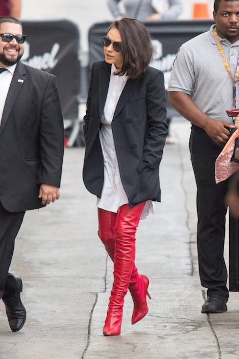 Mila Kunis wears an oversized white blouse with a black blazer over patent red boots in 2017