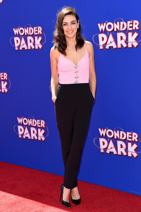 Mila Kunis wears black pants and a light pink top to a film premiere in 2019