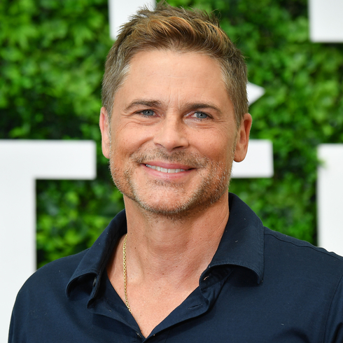 Rob Lowe smiling on a red carpet