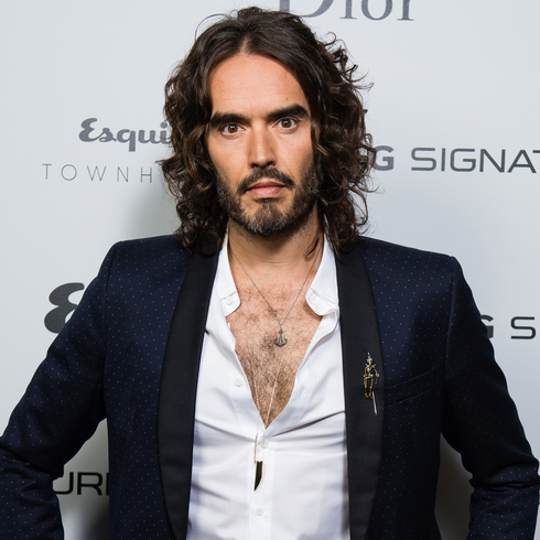 Russell Brand posing in front of a step and repeat