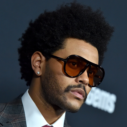 The Weeknd looking serious while wearing sunglasses on a red carpet