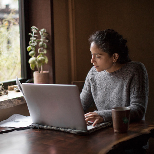 Women sitting by window looking at laptop
