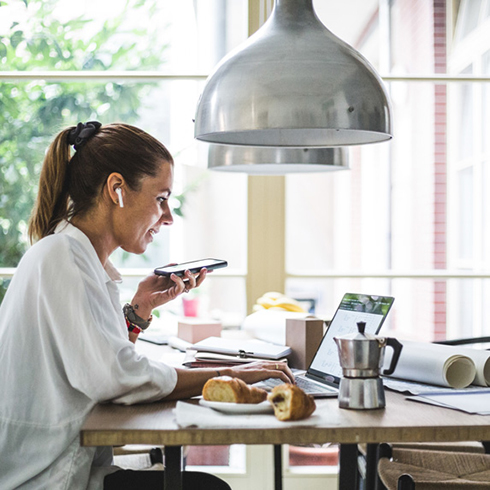 Woman sitting at kitchen table under pendant lighting
