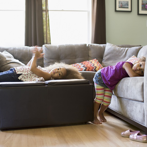 Two young girls laying on couches in living room