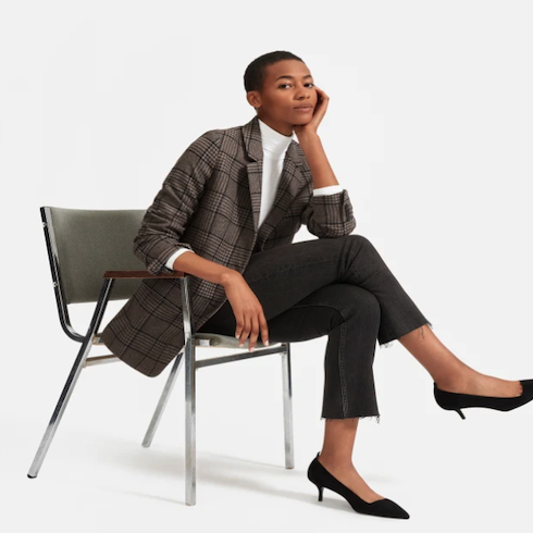 Woman sitting in chair with plaid blazer