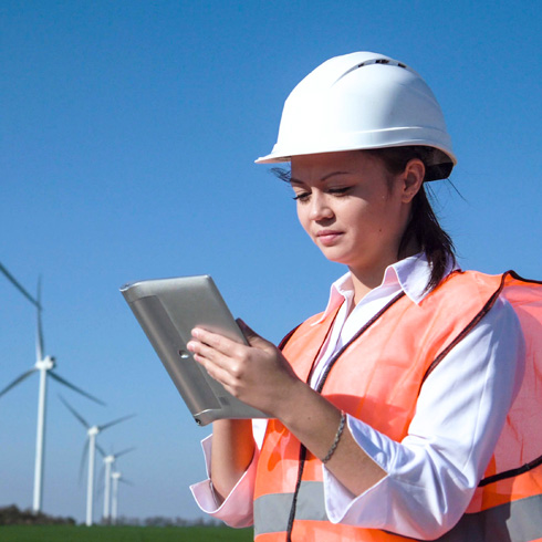Wind turbine service technician checking their tablet