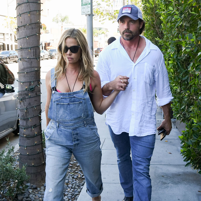 Denise Richards and Aaron Phypers holding hands and walking down a street.