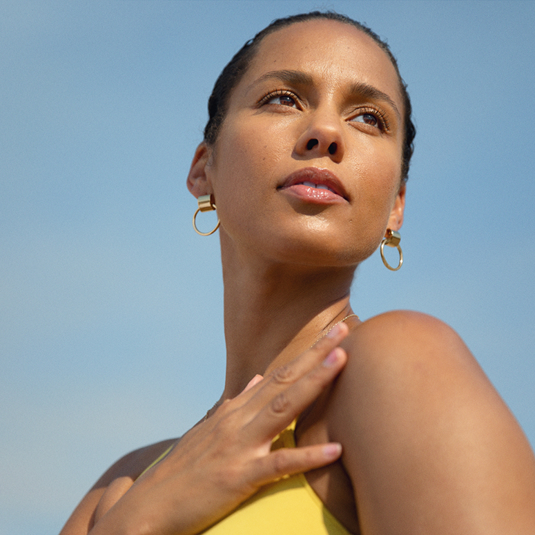 Alicia Keys looking off into the distance against a clear blue sky