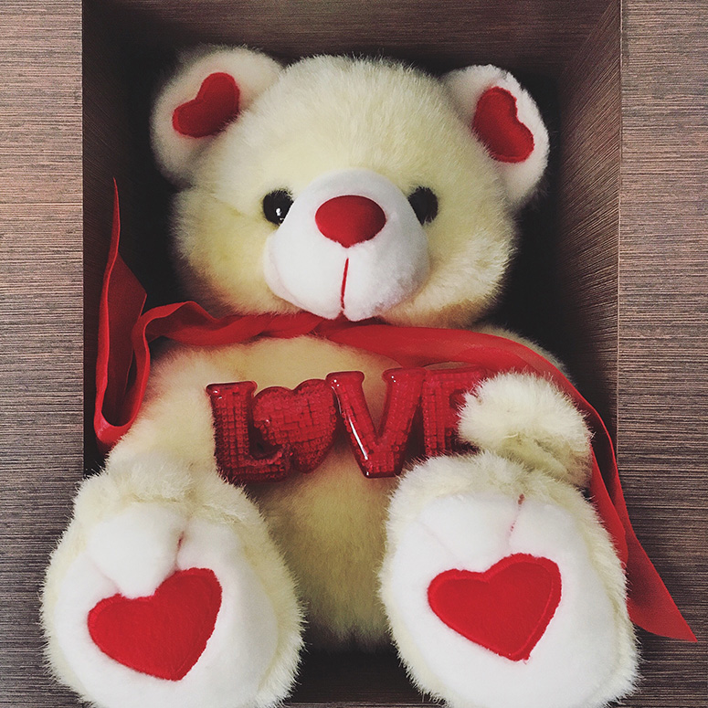 Teddy bear with hearts in a box