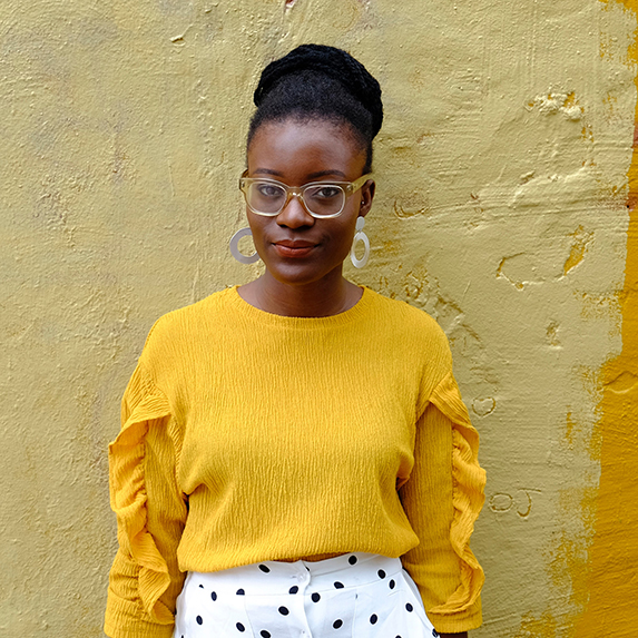 Woman in a mustard yellow sweater against a yellow wall