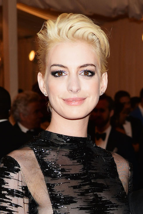 Anne Hathaway wears her hair in a short, platinum-blonde hairstyle