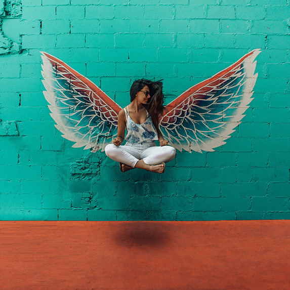 Woman against wall with coloured angel wings, appearing to float