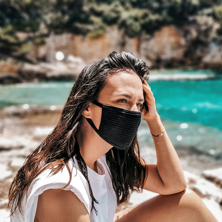 Woman sitting at a beach with a face mask